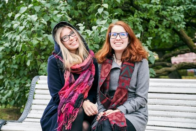 Portret dwóch młodych atrakcyjnych dziewczyn rasy kaukaskiej, ubranych w płaszcz, siedzących na ławce w parku miejskim na tle zielonych liści.