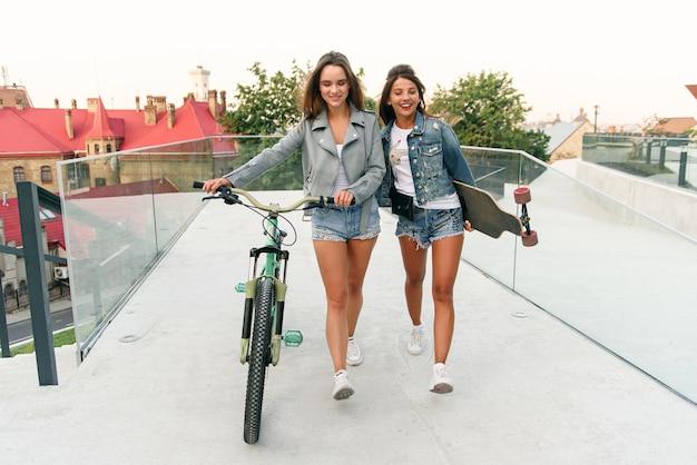 Portret dwóch młodych atrakcyjnych kobiet miejskich spacerujących z rowerem i jeżdżących na deskorolce na ulicy w słoneczny letni dzień ..
