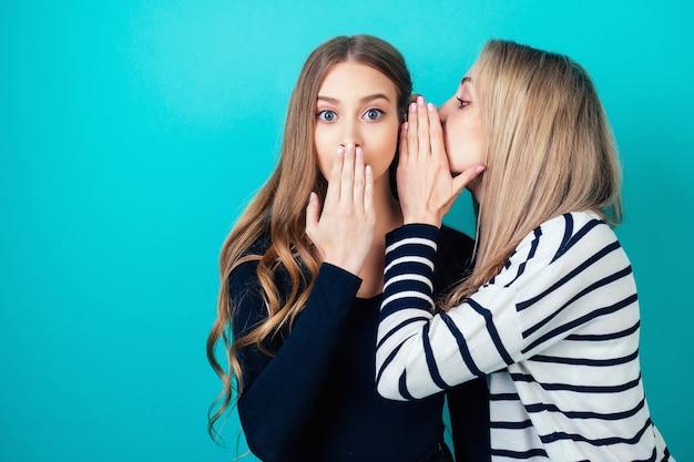 Portret dwóch młodych atrakcyjnych szczęśliwych dziewczyn kobiet z makijażem podsłuchuje szepcze tajną tajemnicę w studio na niebieskim tle. pojęcie plotek i poufności.