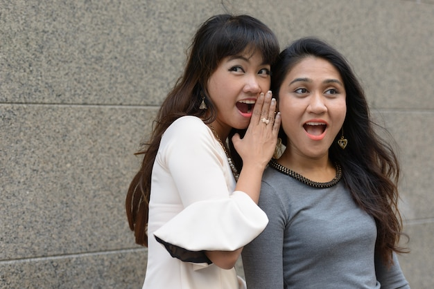 Portret dwóch młodych azjatyckich przedsiębiorców razem w mieście na zewnątrz