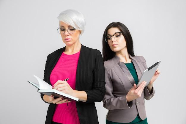 Portret dwóch młodych dam biznesowych w kostiumach na białym tle