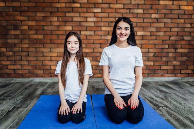 Portret dwóch młodych elastycznych dziewczyn siedzących na macie do jogi i przygotowujących się przed treningiem..