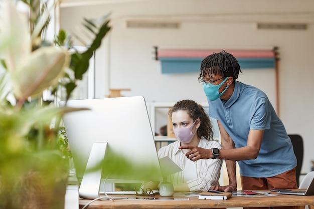 Portret dwóch młodych fotografów w maskach, wskazując na ekran komputera i przeglądając zdjęcia w biurze studio, kopia przestrzeń