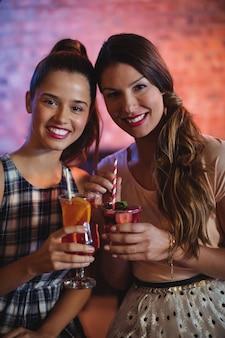 Portret dwóch młodych kobiet o koktajl drinki