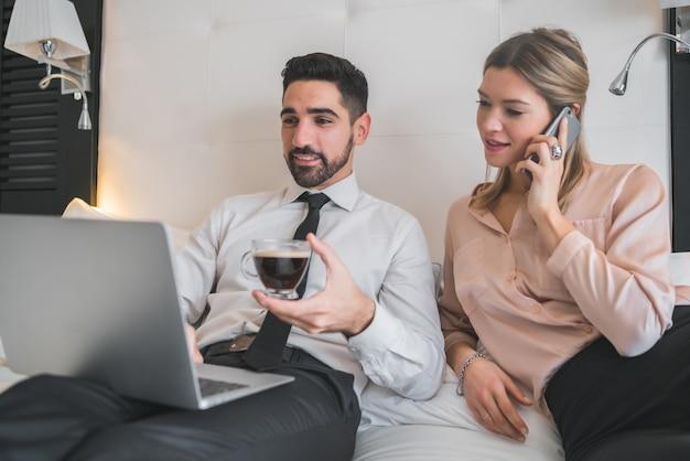 Portret dwóch młodych ludzi pracujących razem na laptopie w pokoju hotelowym. koncepcja podróży biznesowych.