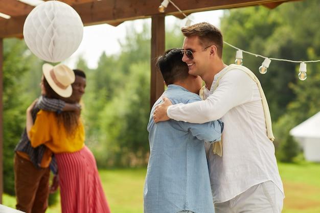 Portret dwóch młodych mężczyzn przytulanie podczas powitania na imprezie na świeżym powietrzu latem