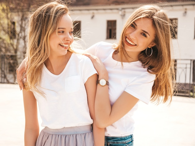 Portret dwóch młodych pięknych blond uśmiechnięte dziewczyny hipster w modne letnie białe ubrania t-shirt. . pozytywne modele zabawy