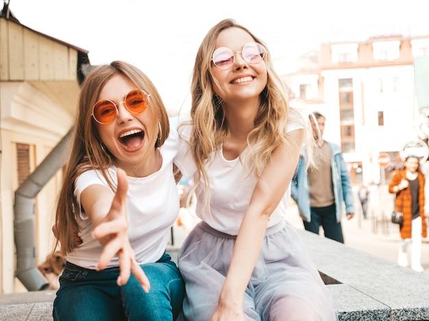 Portret dwóch młodych pięknych blond uśmiechnięte dziewczyny hipster w modne letnie białe ubrania t-shirt. seksowne beztroskie kobiety siedzi na ulicie. pozytywne modele zabawy w okularach przeciwsłonecznych