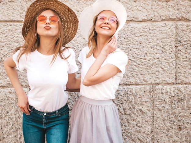 Portret dwóch młodych pięknych blond uśmiechnięte dziewczyny hipster w modne letnie białe ubrania t-shirt. .