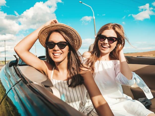 Portret dwóch młodych, pięknych i uśmiechniętych hipster kobiet w kabriolecie