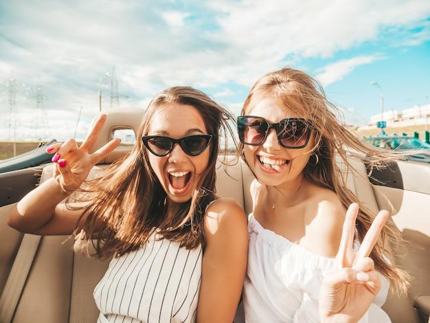 Portret dwóch młodych, pięknych i uśmiechniętych hipsterek w kabriolecie