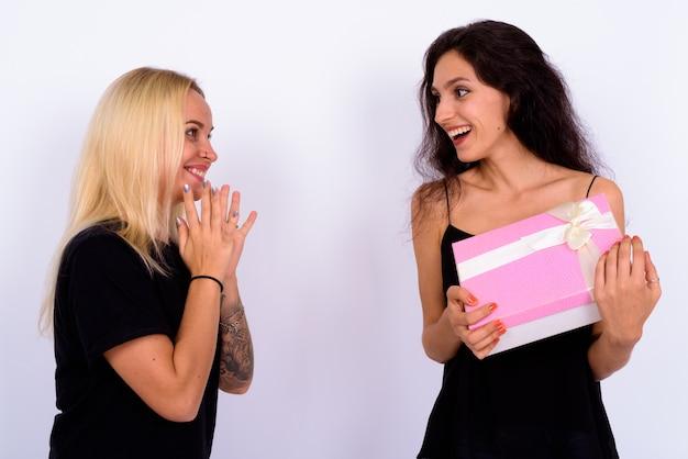 Portret dwóch młodych pięknych kobiet razem przeciw białej ścianie