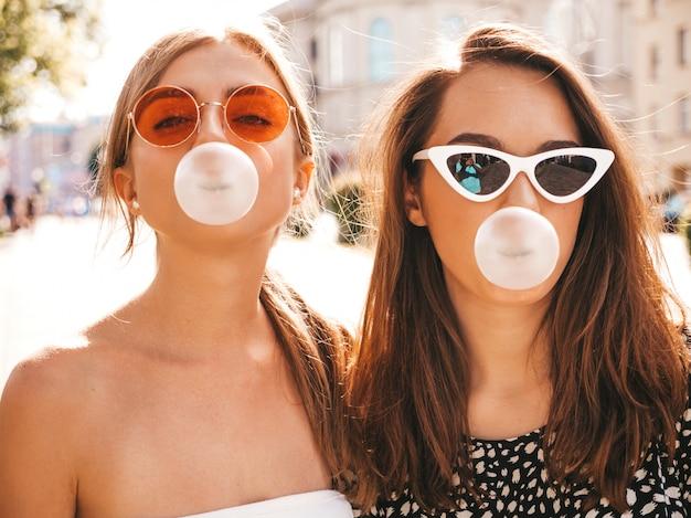 Portret dwóch młodych pięknych uśmiechniętych hipster dziewcząt w modne letnie ubrania