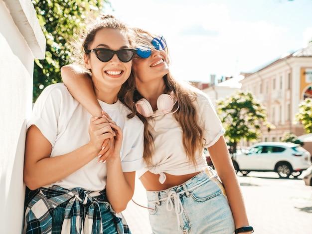 Portret dwóch młodych, pięknych, uśmiechniętych hipsterskich dziewczyn w modnych letnich białych t-shirtach!