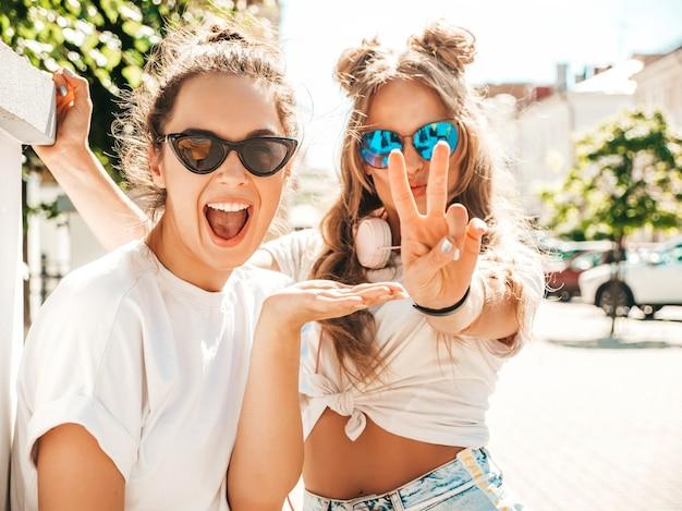 Portret dwóch młodych, pięknych, uśmiechniętych hipsterskich kobiet w modnych letnich białych t-shirtach!