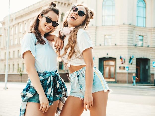 Portret dwóch młodych, pięknych, uśmiechniętych kobiet hipster w modnych letnich białych t-shirtach!