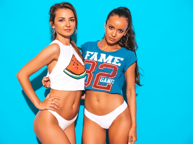 Portret dwóch młodych pięknych uśmiechniętych seksownych kobiet w białych letnich majtkach i temacie. modne dziewczyny zabawy. pozytywne modele