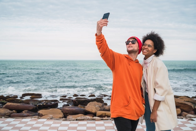 Portret dwóch młodych przyjaciół spędzających miło czas razem i robienie selfie ze smartfonem na świeżym powietrzu nad morzem.