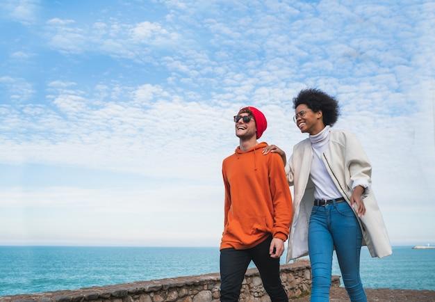 Portret dwóch młodych przyjaciół spędzających miło czas razem, spacerując po wybrzeżu i dobrze się bawiąc.