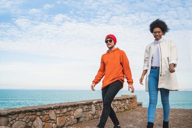 Portret dwóch młodych przyjaciół spędzających miło czas razem, spacerując po wybrzeżu i dobrze się bawiąc