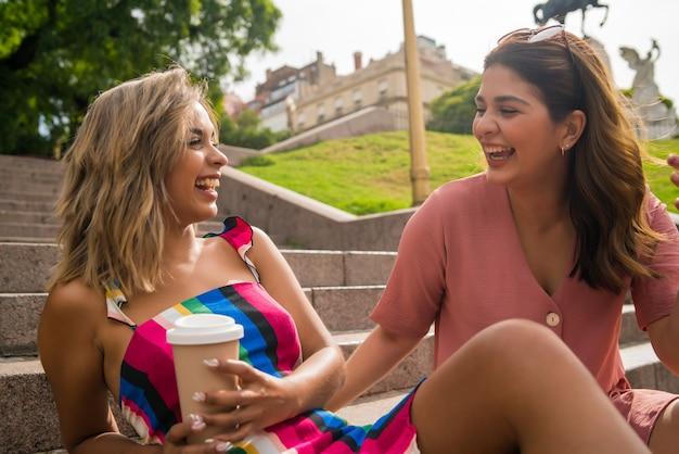 Portret dwóch młodych przyjaciół spędzających razem czas i rozmawiających, siedząc na schodach na świeżym powietrzu. koncepcja urbanistyczna.