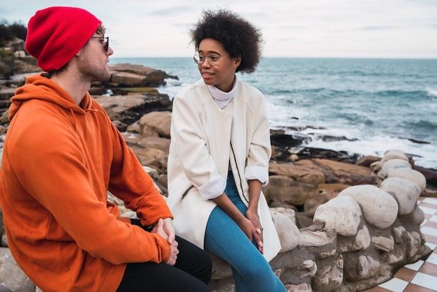 Portret dwóch młodych przyjaciół spędzających razem miło czas i rozmawiając, siedząc nad morzem w.