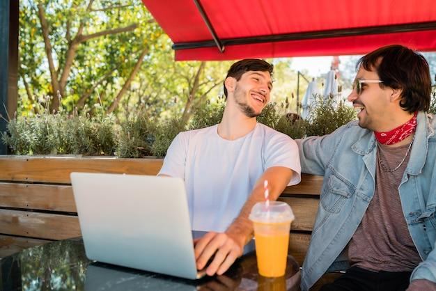 Portret dwóch młodych przyjaciół za pomocą laptopa siedząc na zewnątrz w kawiarni. koncepcja przyjaźni i technologii.
