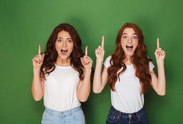 Portret dwóch młodych rudowłosych kobiet w wieku 20 lat w białych koszulkach, uśmiechniętych i wskazujących palcami w górę z podniecenia, odizolowanych na zielonym tle