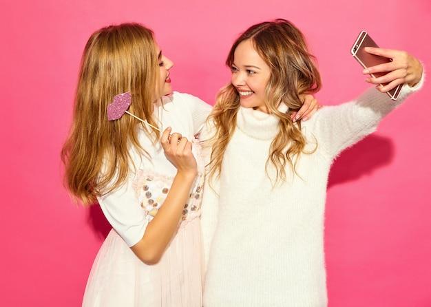 Portret dwóch młodych stylowych uśmiechniętych blond kobiet