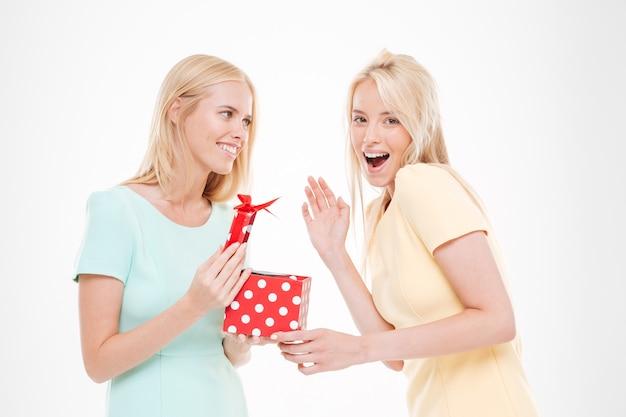 Portret dwóch młodych szczęśliwych kobiet z prezentem na białym tle nad białą ścianą