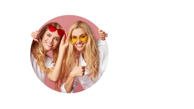 Portret dwóch młodych szczęśliwych, zszokowanych kobiet w okularach w kształcie serca, wyglądających na białą dziurę w ścianie. wielka wyprzedaż. śmieszne twarze. puste miejsce na tekst