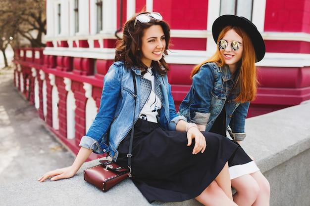Portret dwóch najlepszych przyjaciół, śmiejąc się i rozmawiając na świeżym powietrzu na ulicy w centrum miasta