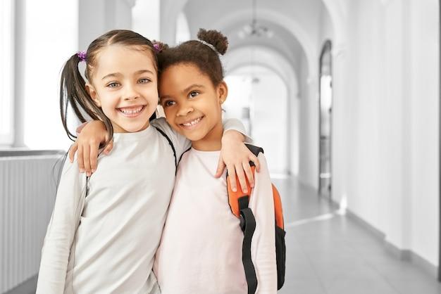 Portret dwóch najlepszych przyjaciółek dziewczynki w szkole stojącej na korytarzu, obejmując się i uśmiechając.