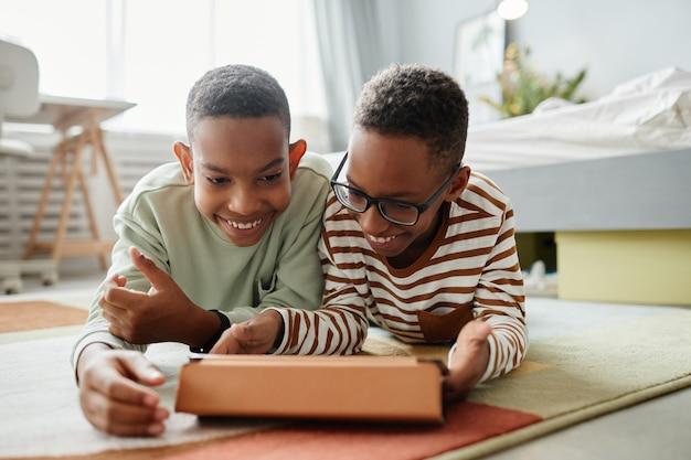 Portret dwóch nastoletnich chłopców z afryki, korzystających razem z cyfrowego tabletu, leżąc na podłodze w...
