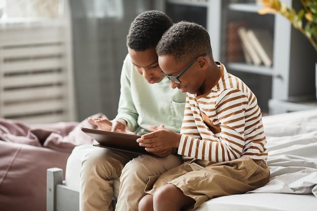Portret dwóch nastoletnich chłopców z afryki, korzystających razem z cyfrowego tabletu, siedząc na łóżku w...