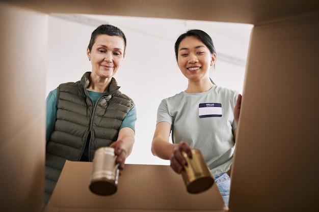Portret dwóch ochotniczek wkładających konserwy do pudełek podczas akcji pomocy i darowizn