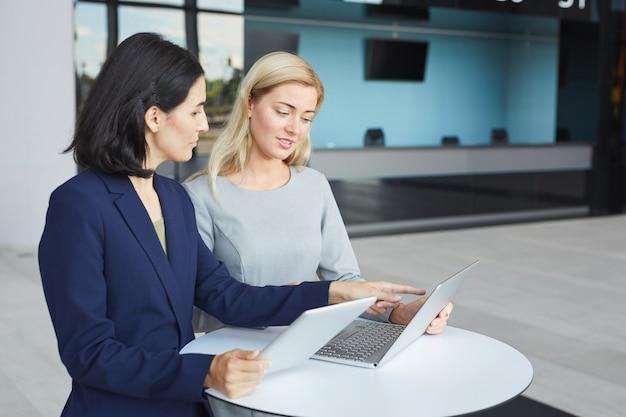 Portret dwóch odnoszących sukcesy biznesmenek rozmawiających o pracy, stojąc przy biurku w biurowcu i używając laptopa,
