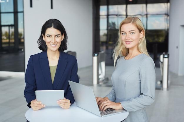 Portret dwóch odnoszących sukcesy biznesmenek uśmiecha się do kamery, stojąc przy biurku w biurowcu i trzymając laptopa