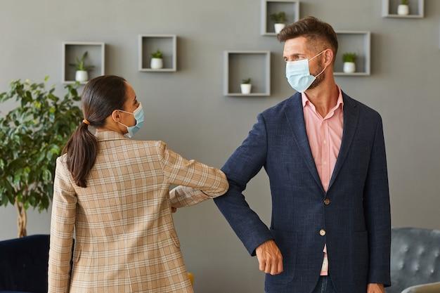 Portret dwóch odnoszących sukcesy biznesmenów w maskach i uderzających łokciami w talii jako bezdotykowe powitanie w biurze po pandemii