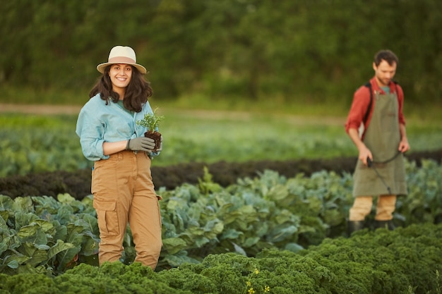 Portret dwóch osób pracujących w polu na plantacji warzyw, skupić się na młodej kobiety uśmiechając się do kamery na pierwszym planie, kopia przestrzeń