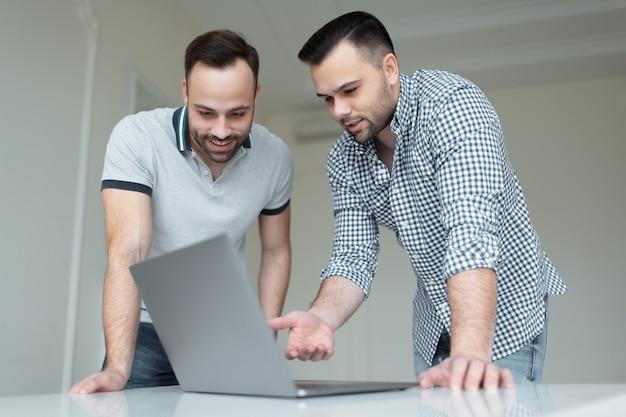 Portret dwóch pewny siebie biznesmen pracuje na laptopie. jeden mężczyzna rozmawia na smartfonie, gdy inny facet wskazuje palcem na ekranie.