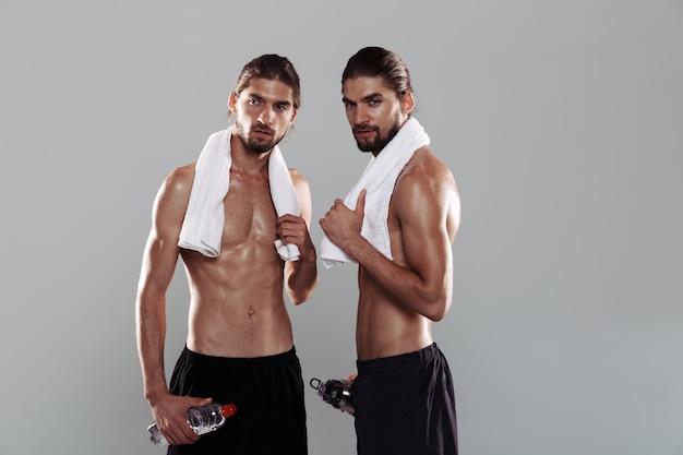 Portret dwóch pewnych siebie, muskularnych, bez koszuli braci bliźniaków