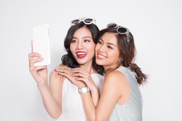 Portret dwóch pięknych azjatyckich modnych kobiet biorących selfie