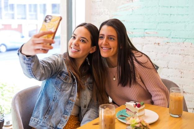 Portret dwóch pięknych dziewczyn, biorąc zdjęcie selfie w kawiarni