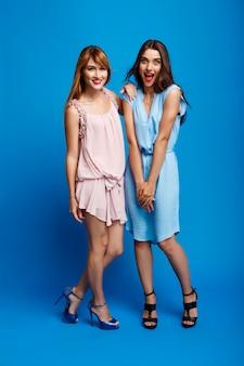 Portret dwóch pięknych dziewczyn na niebieską ścianą