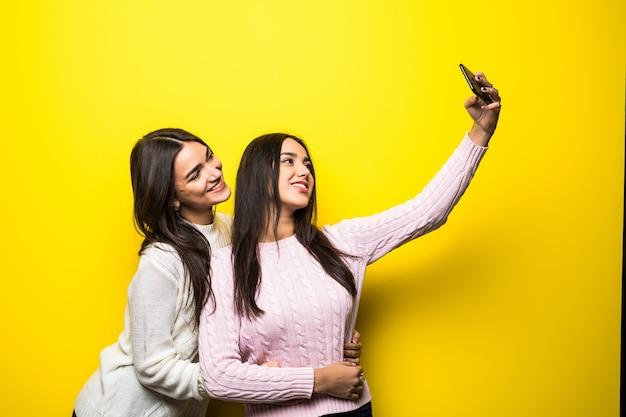 Portret dwóch pięknych dziewczyn ubranych w swetry, stojąc i biorąc selfie na białym tle nad żółtą ścianą