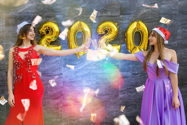 Portret dwóch pięknych dziewczyn w sylwestra w eleganckich sukniach wieczorowych