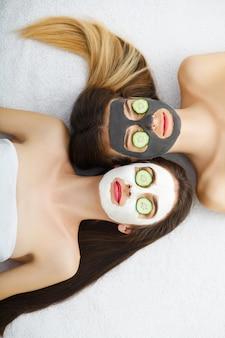 Portret dwóch pięknych dziewczyn z kremem do twarzy na twarzach, patrząc w kamerę i leżąc twarzą w twarz na podłodze i uśmiechając się