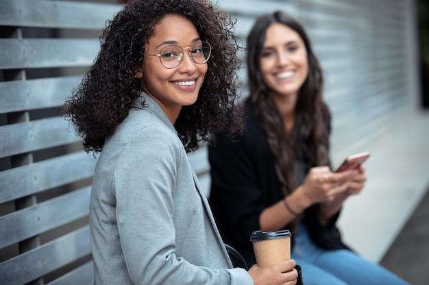 Portret dwóch pięknych kobiet biznesu za pomocą smartfona, patrząc na kamery, siedząc na ławce na ulicy.