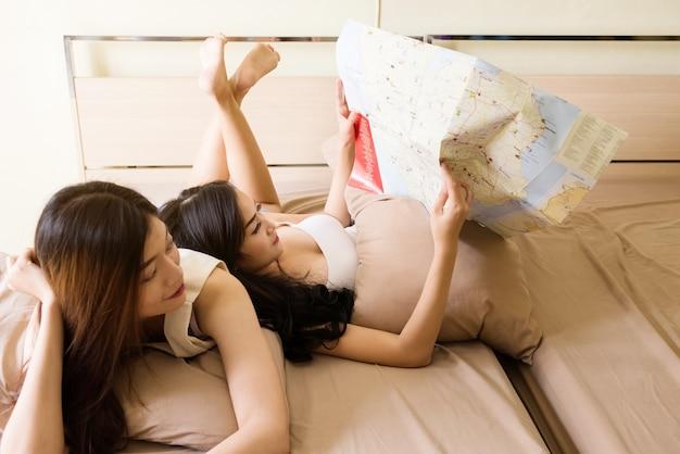 Portret dwóch pięknych lesbijek lub współlokatora szczęśliwe kobiety razem spojrzeć na mapę.